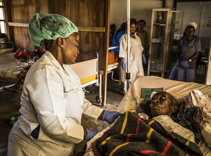 A health worker with a white coat and hair net touches a patient lying on a bed
