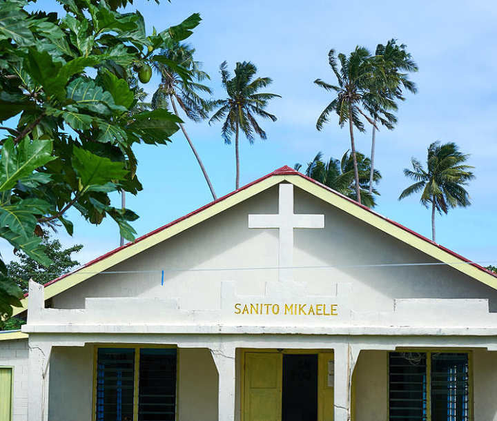 The roofline of a church against a backdrop of blue sky and palm trees