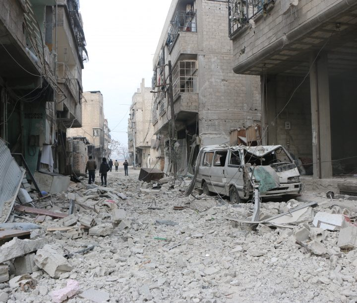 A street covered in rubble with damaged buildings lining either side